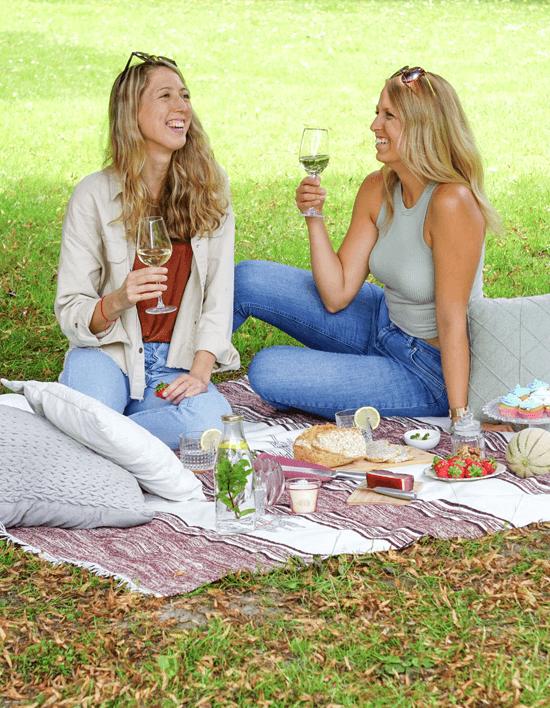 Zwei Frauen auf Picknickdecke in Park, beide haben Weinglas in der Hand