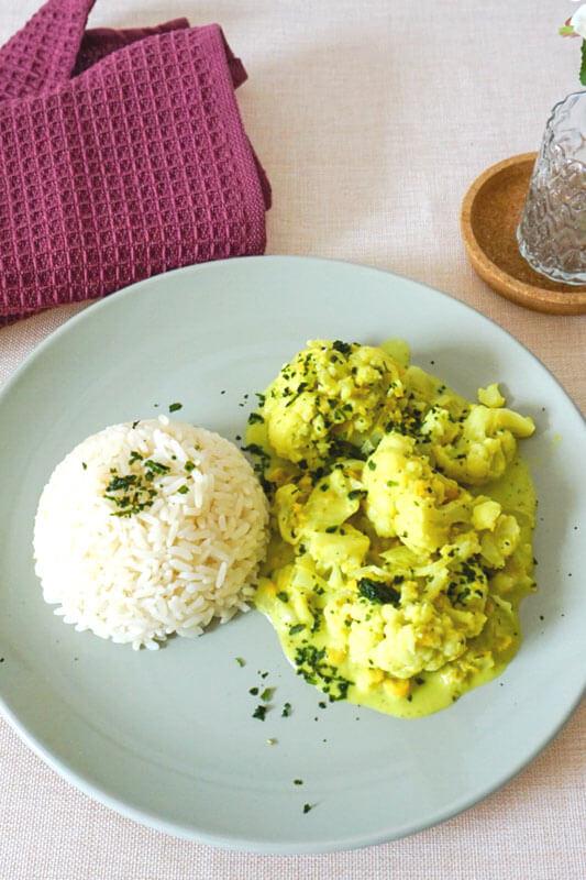 Blumenkohl-Kicherernsen-Curry auf blauem Teller mit Reis als Beilage steht auf Tisch