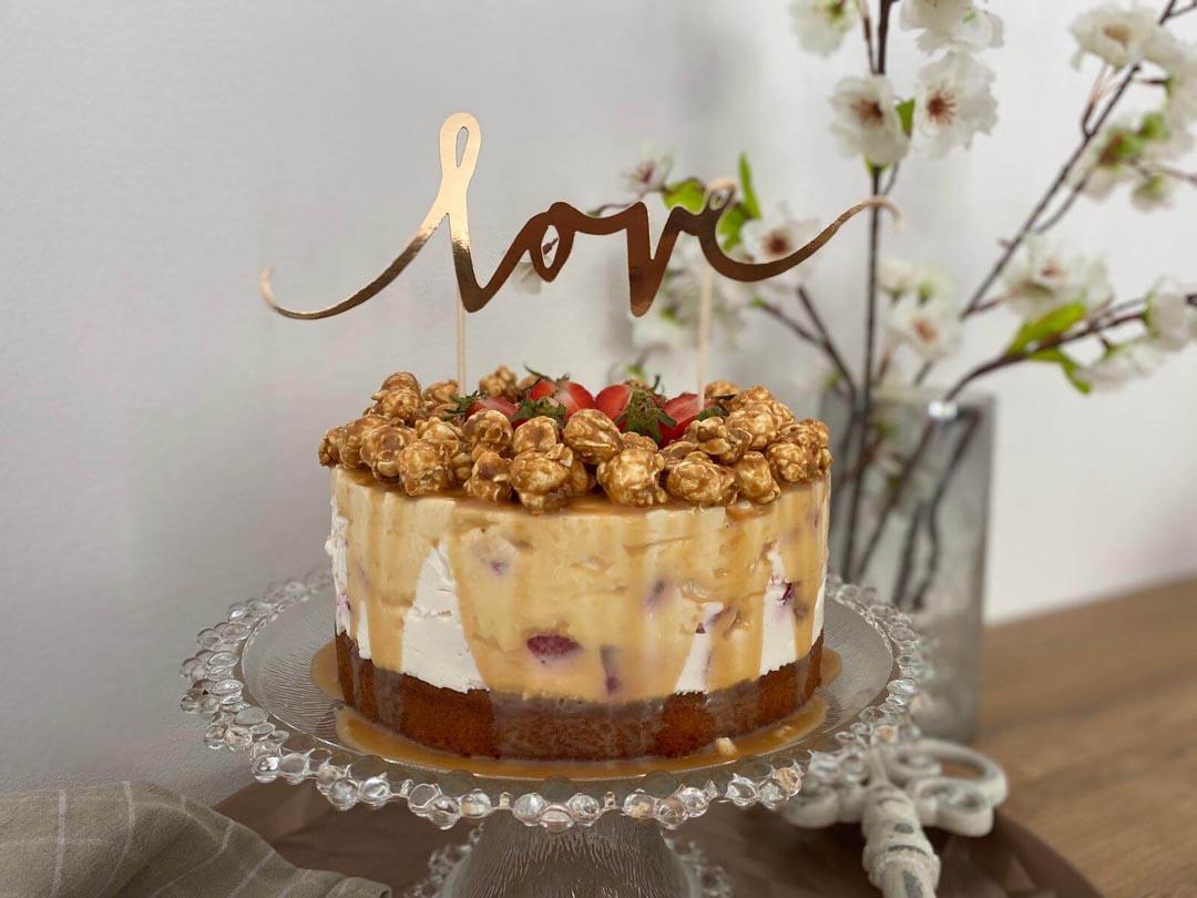 Erdbeer-Torte mit Karamell und Popcorn steht auf Etagere auf Küchentisch