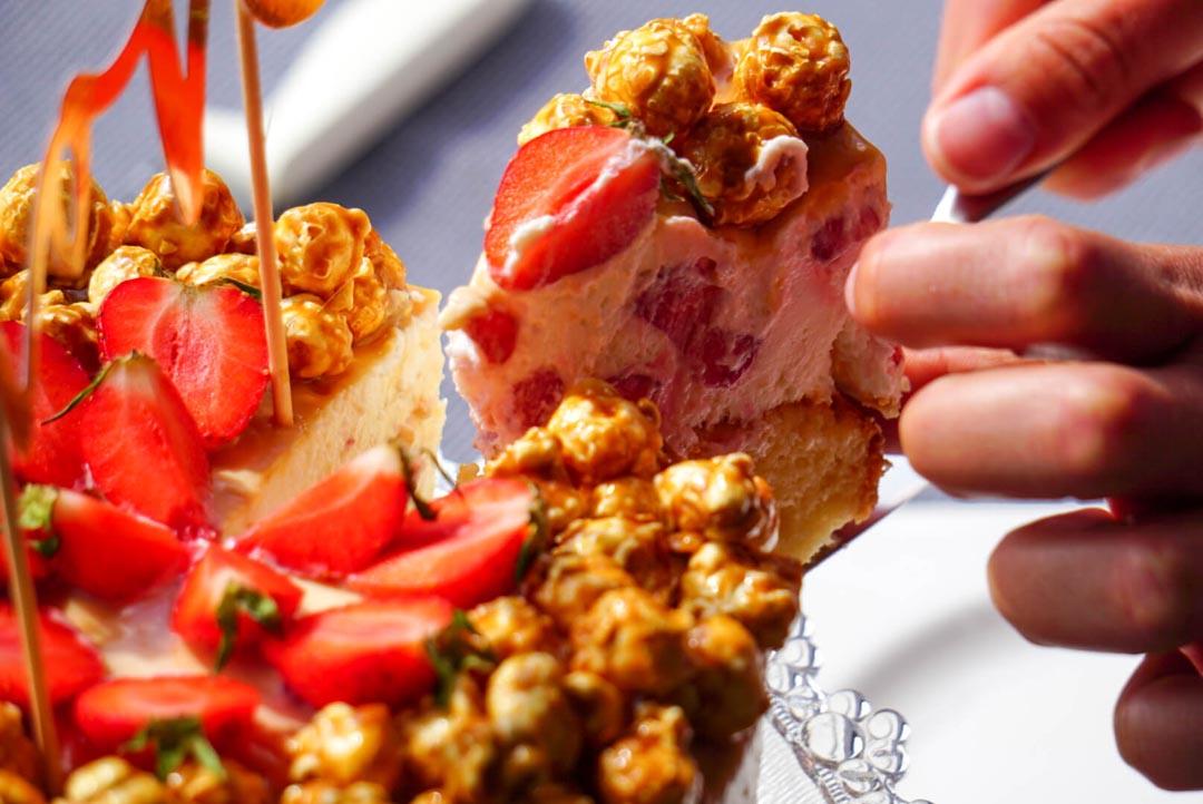 Erdbeer-Torte mit Karamell und Popcorn wird angeschnitten
