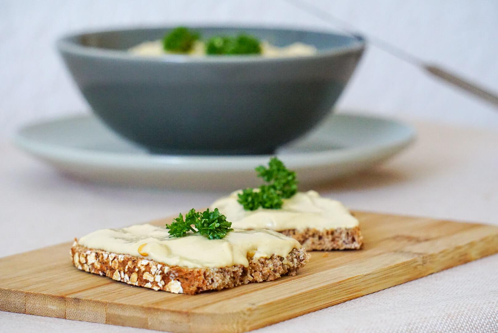 Zwei Brote mit Hummus liegen auf einem Holzbrettchen. Dahinter steht eine Schale mit Hummus. Zubereitet nach Hummus Rezept
