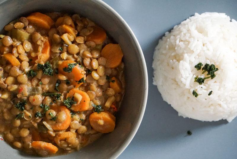 Nahuafnahme Eine Schale mit Kokos-Linsen-Curry, dazu Reis