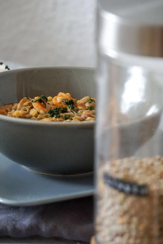 Eine Schale mit Kokos-Linsen-Curry, dazu Reis im Hintergrund, Vordergrund zeigt unscharf ein Glas mit Linsen