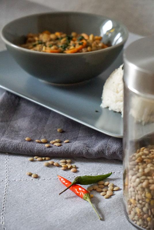Eine Schale mit Kokos-Linsen-Curry, dazu Reis unscharf im Hintergrund, Vordergrund zeigt ein Glas mit Linsen