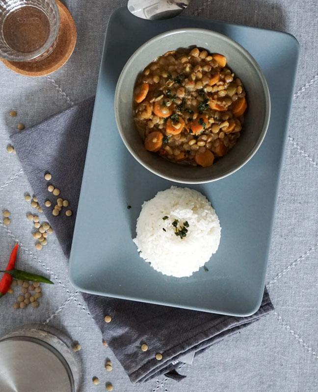 Eine Schale mit Kokos-Linsen-Curry, dazu Reis, von oben fotografiert