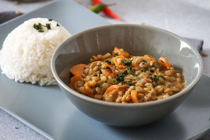 Eine Schale mit Kokos-Linsen-Curry, dazu Reis