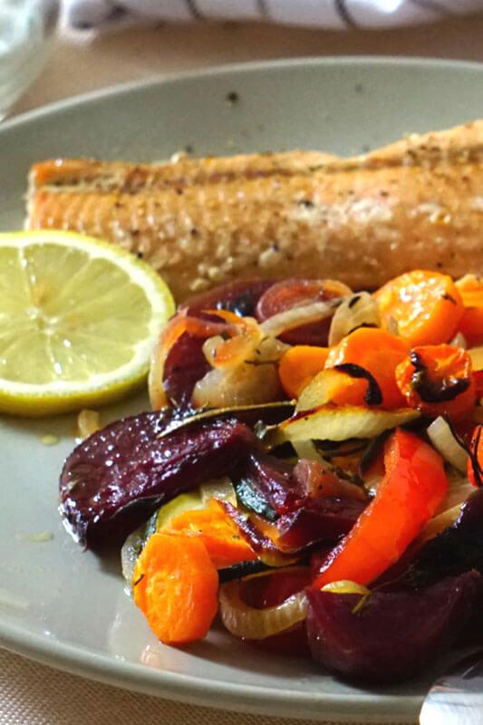 Nahaufnahme von Im Ofen gebackene Rote-Beete, Parpika und Möhren auf einem Telller mit Lachs