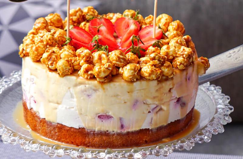 Erdbeer-Torte mit Karamell und Popcorn, auf gartentisch, Topping im Fokus