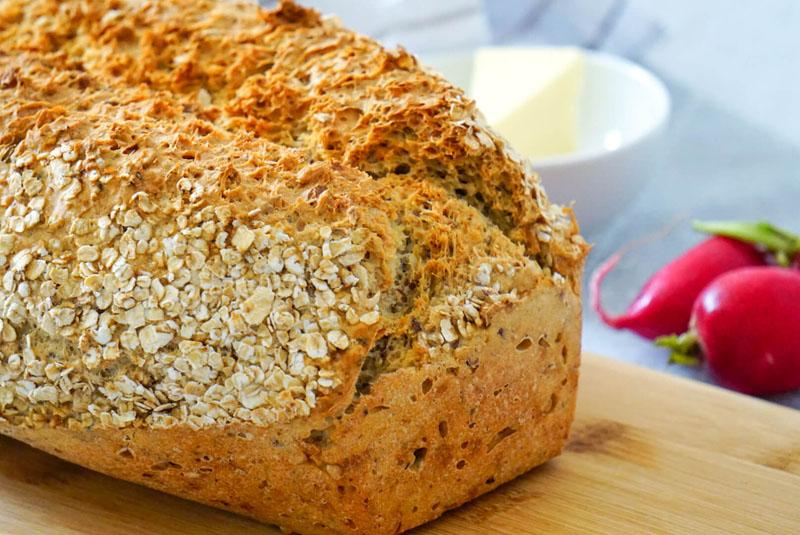Selbstgebackener frischer Brotlaib liegt auf Holzbrett