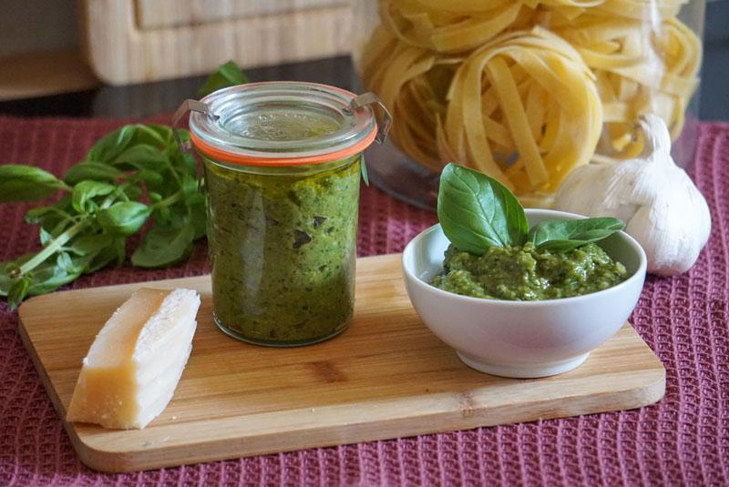 Einfaches Pesto verde in Schälchen und im Weckglas, daneben Nudeln, Basilikum und Knoblauch