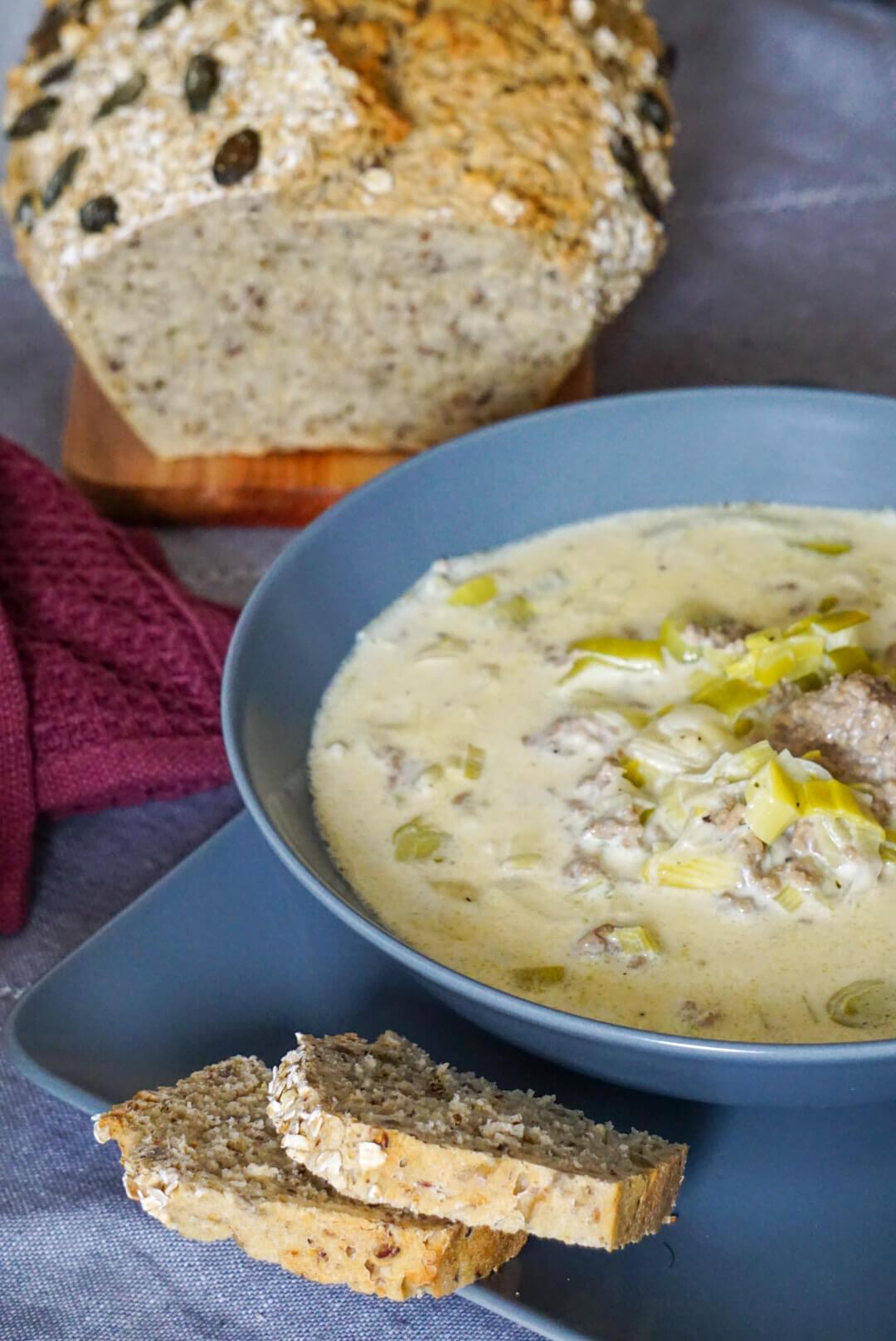 Ein Teller mit Käse-Lauch-Suppe daneben ein Stück Brot