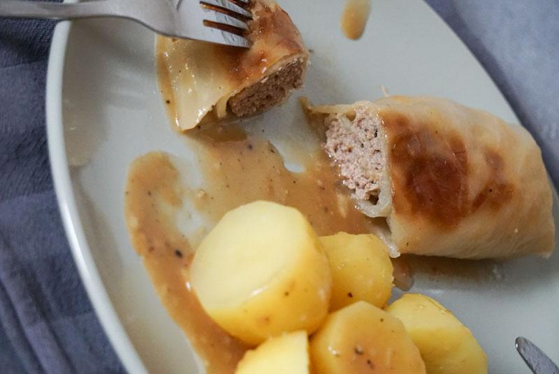 angeschnittene Kohlroulade auf Teller, dazu Salzkartoffeln