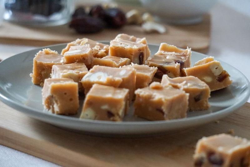 Kleine Stücle Karamell-Fudge auf Holzbrett, dazu Datteln und Cashewkerne